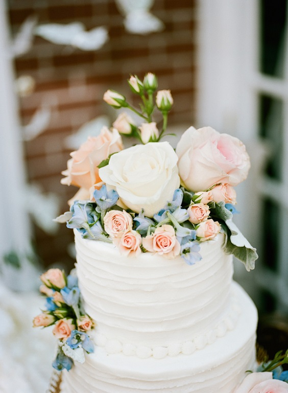 white wedding cake with dusty blue and blush florals for march wedding colors 2022 dusty blue white and blush