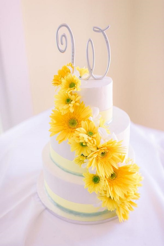 white wedding cake dotted with yellow flowers for April wedding colors 2022 mint yellow and white