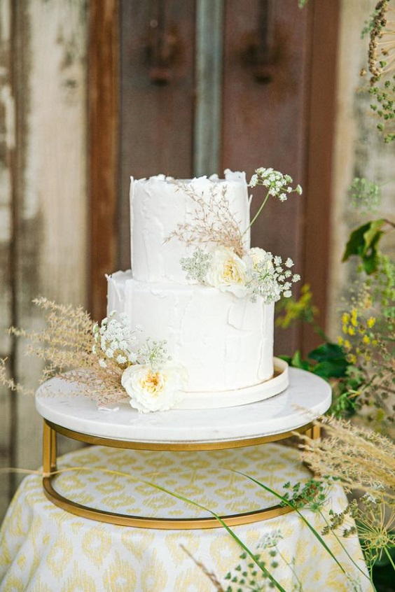wedding cake dotted with pale yellow flowers for April wedding colors 2022 pale yellow and white colors