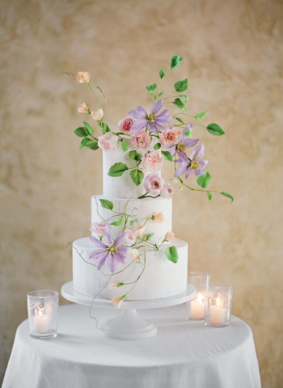 wedding cake dotted with lavender flowers and greenery for April wedding colors 2022 light pink pale yellow and gold colors
