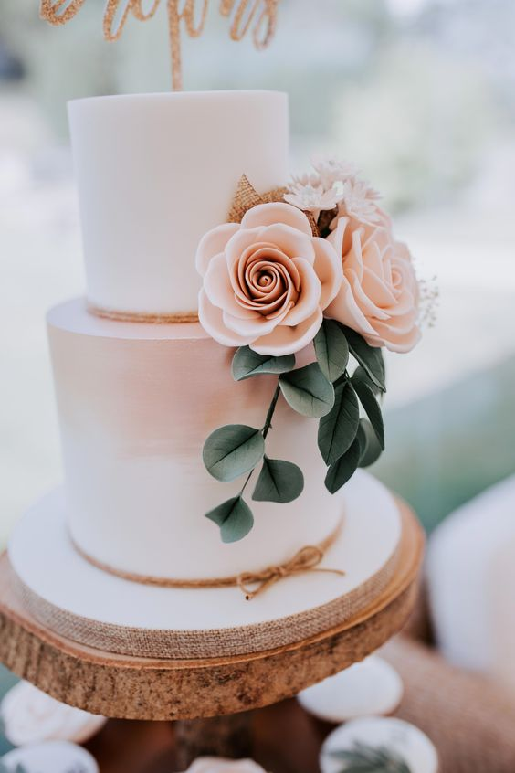 blush wedding cake dotted with blush flowers greenery for summer wedding color 2022 blush and sage
