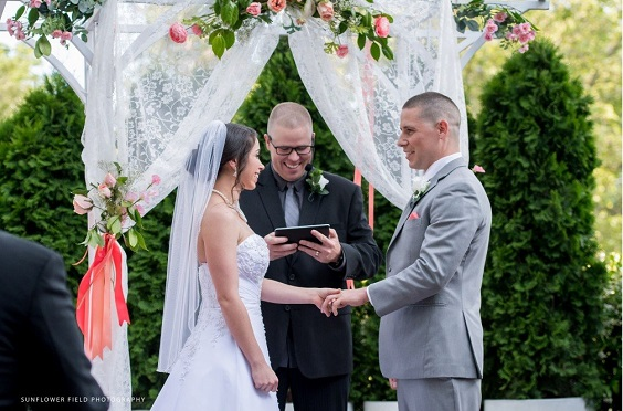wedding arch decorated with coral flowers and greenery for summer wedding color 2022 coral and grey colors
