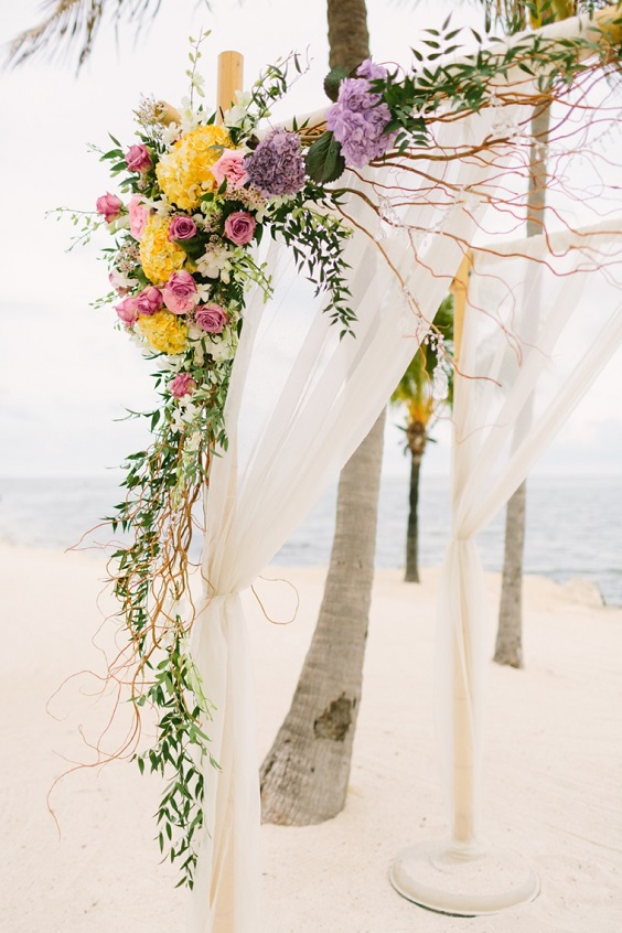 wedding arch decorated with flowers in yellow pink purple for spring wedding color palettes yellow pinkk purple colors