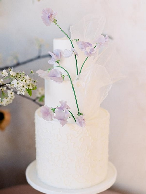 white wedding cake dotted with purple flower for spring wedding color palettes yellow pink purple colors