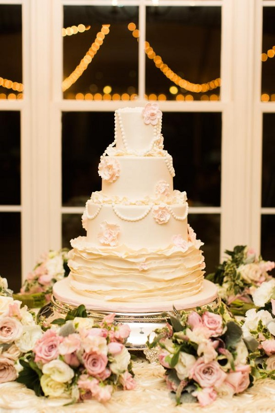 wedding cake dotted with pink flowers and greenery for spring wedding color palettes emerald gold pink colors