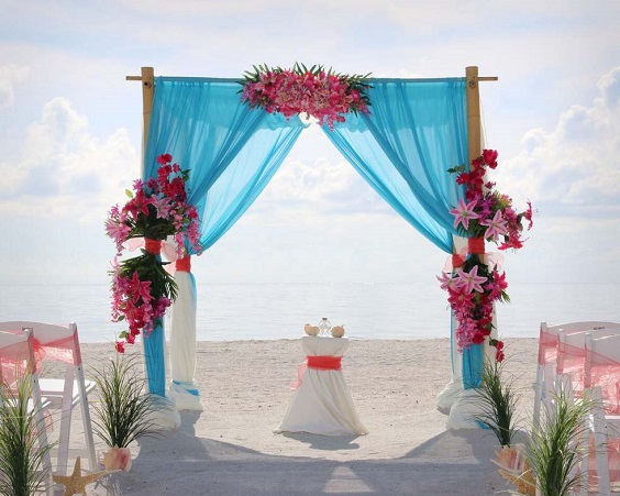 wedding arch with turquoise cloth fuschia flowers for sping wedding colors 2022 fuschia turquoise gold colors