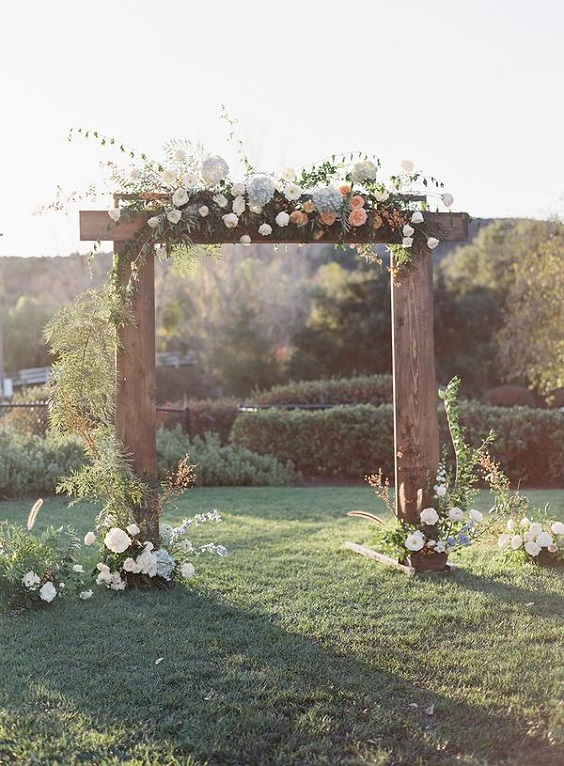 wedding arch with dusty blue and peach flowers for spring wedding colors 2022 dusty blue peach greenery