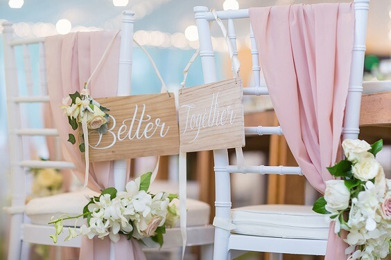white chairs with dusty rose drapes and white and yellow flowers for spring dusty rose wedding